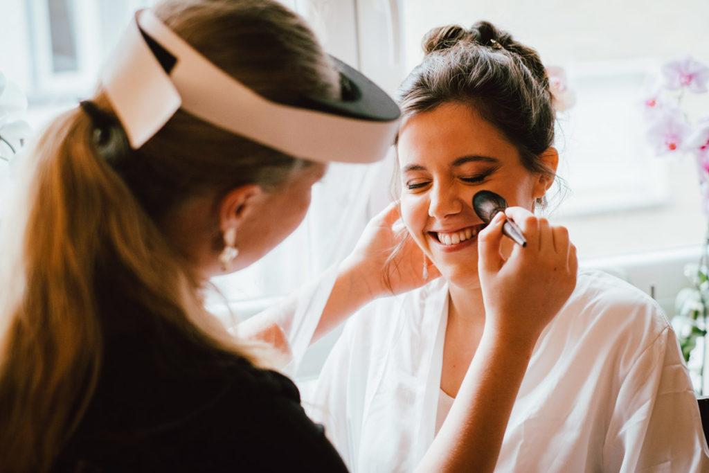 Préparatifs de la mariée en train de se faire maquiller chez ses parents